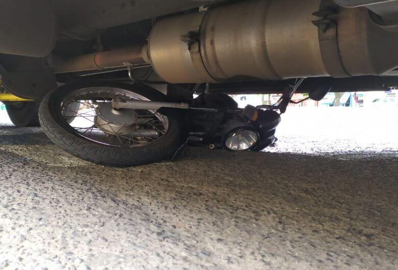 Após colisão, moto fica embaixo de ônibus no centro