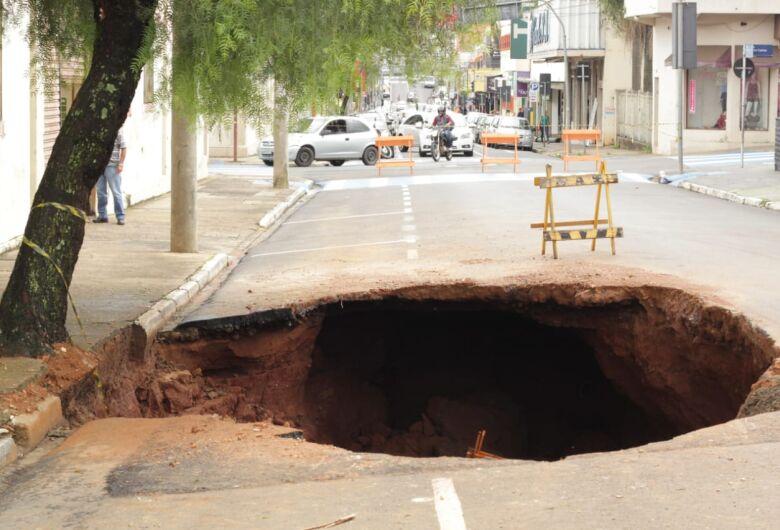"""Cratera """"engole"""" rua no centro e árvore ameaça cair"""