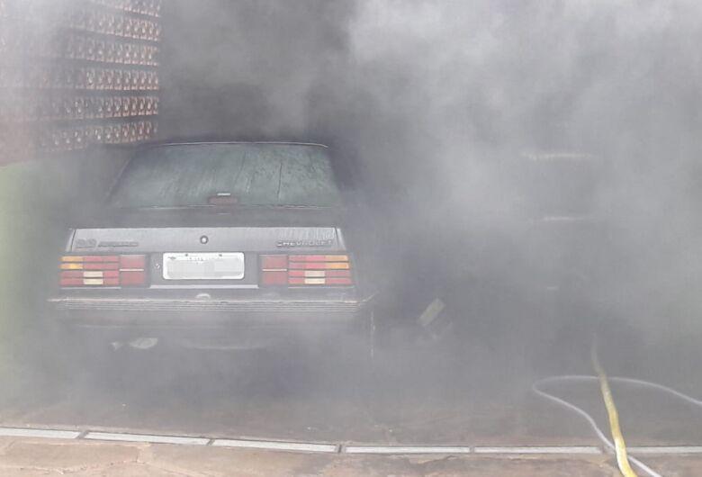 Carro pega fogo em garagem de residência