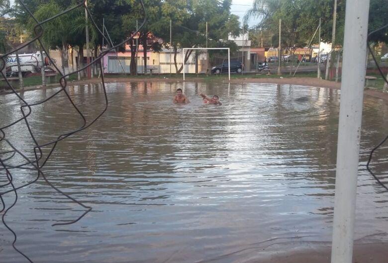 """Moradores """"nadam"""" em campinho de futebol alagado no Cidade Aracy"""
