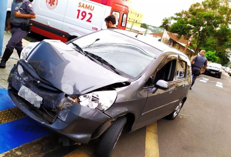 Van avança pare, é atingida por carro e bate em grade no Centro