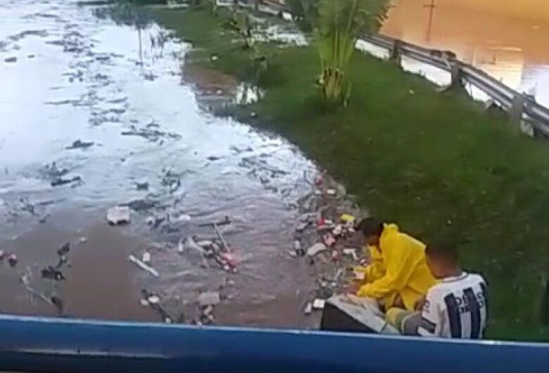 """Jovens se arriscam """"pescando"""" objetos levados pela enchente em córrego"""