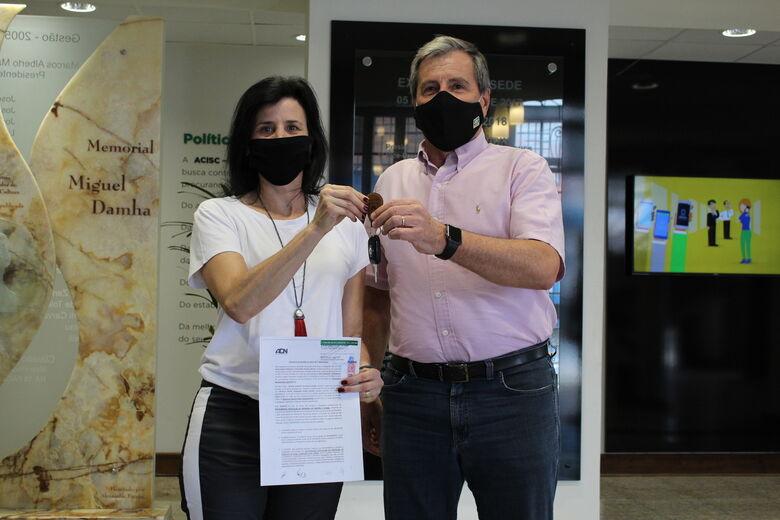 Ganhadora recebe chaves do carro e escritura do apartamento da campanha Natal Premiado ACISC -