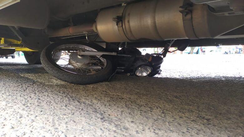 Moto foi parar embaixo do ônibus após a colisão lateral - Crédito: Maycon Maximino