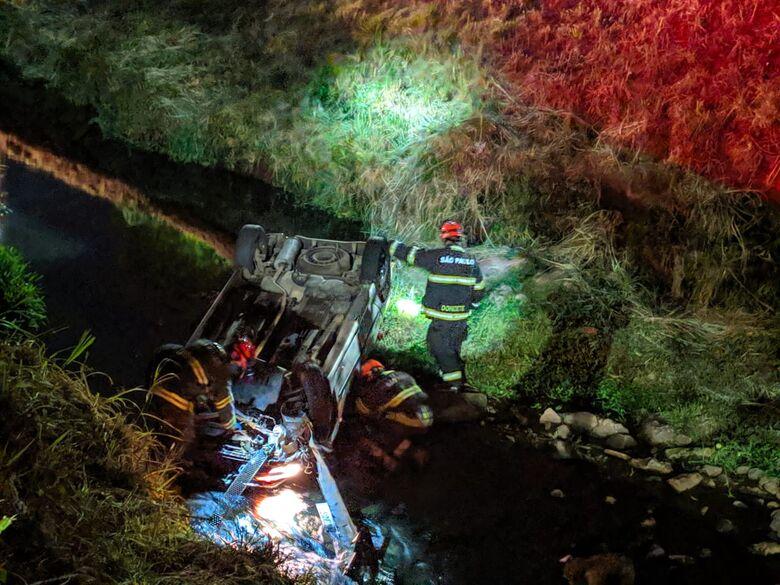 Membros do Corpo de Bombeiros durante o socorro ao motorista do veículo que caiu no córrego - Crédito: Maycon Maximino