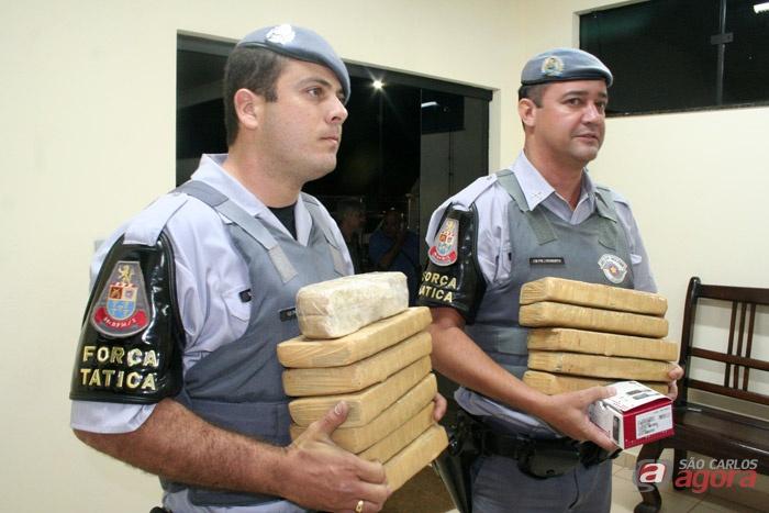 Policiais seguram tijolos de maconha encontrados na residência. Além da droga, os PMs localizaram dinheiro, munições e balança de precisão, além de uma motocicleta. -