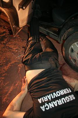 Corpo de vigilante ficou caído ao lado do veículo da empresa -