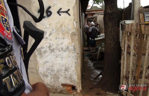 Policiais vistoriam residência durante operação no Jardim Gonzaga. -