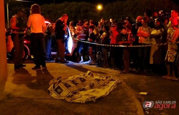 Populares observam o corpo da vítima caido na calçada. (foto: Marcio David) -