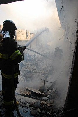 Bombeiro combate as chamas dentro da tapeçaria. (Vinicius Neo/SCA). -