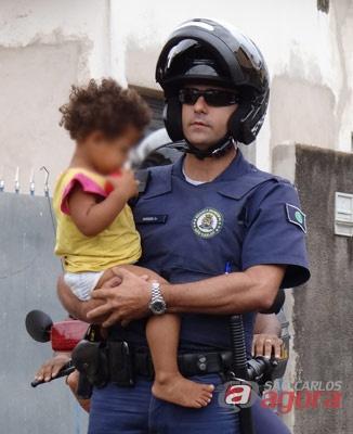 Policial segura uma das crianças que foi retirada da mãe. (foto Marcio David). -