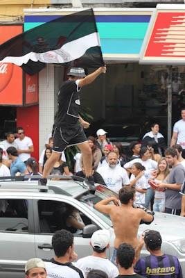 Torcedor sobe no teto de carro para comemorar a conquista. (foto Mauricio Duch). -