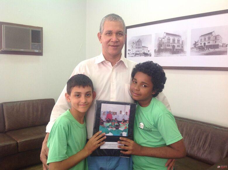 Lucão, entre os alunos Juan e Kennedy, que são atendidos por projetos da Casa da Criança -