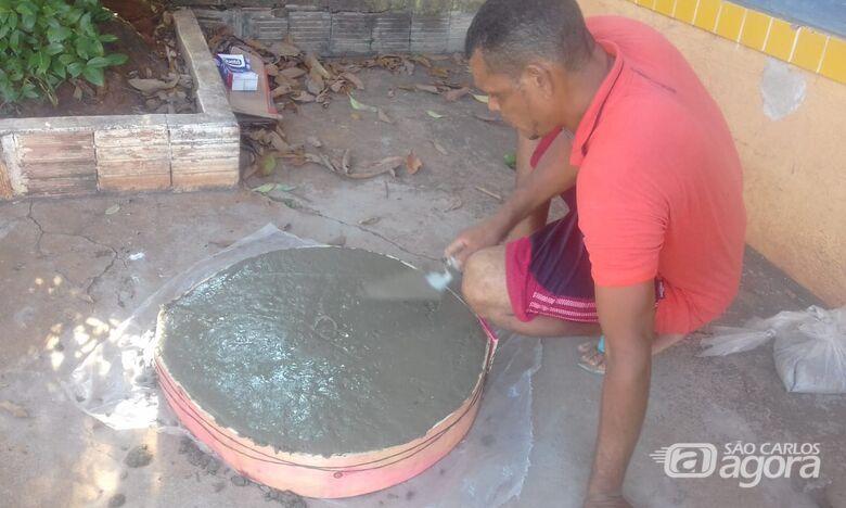 Para evitar acidentes, pedreiro faz tampa para bueiro em rua - Crédito: Divulgação