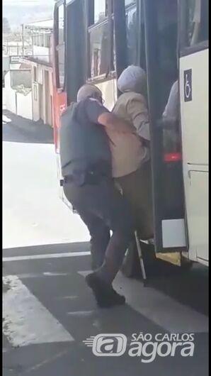 Policial militar carrega idosa com dificuldade de locomoção no colo para ajudá-la a subir no ônibus -