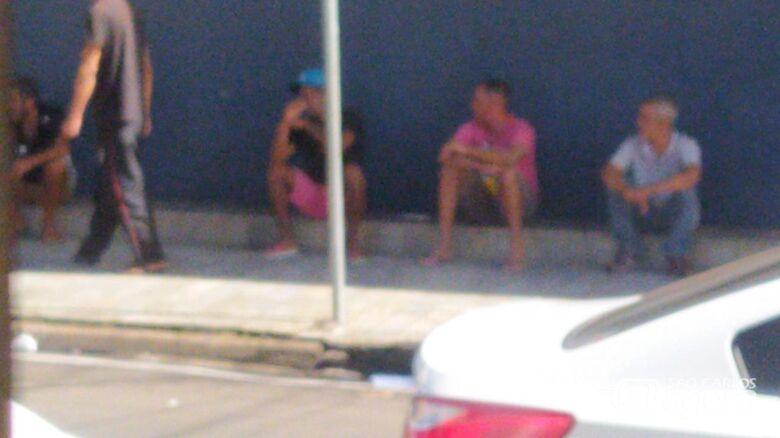 Sentados, eles ingerem 'corotes' de bebida alcoólica - Crédito: Divulgação