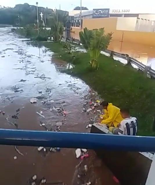 """Jovens se arriscam """"pescando"""" objetos levados pela enchente em córrego -"""